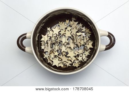 A lot of wooden stars at the bottom of the soup tureen on white background.