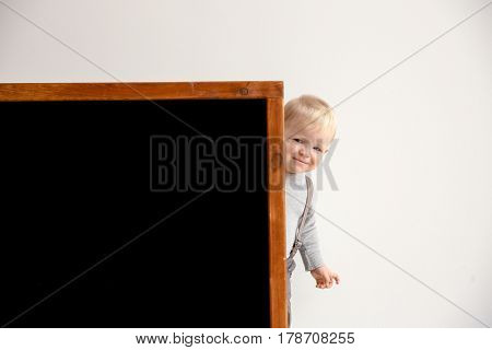Cute little boy and blackboard on light background
