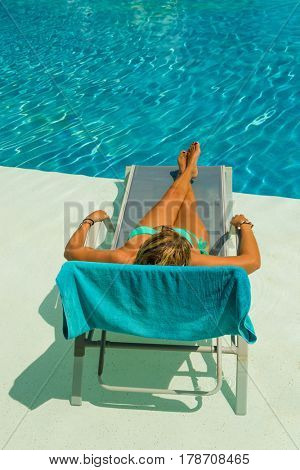 woman enjoying on sunbed at the swimming pool