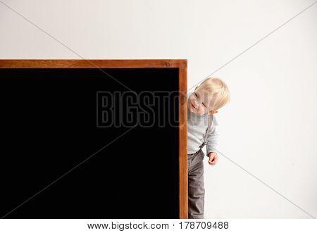 Cute little boy and blackboard near light wall