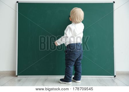 Cute little boy writing on blackboard in classroom