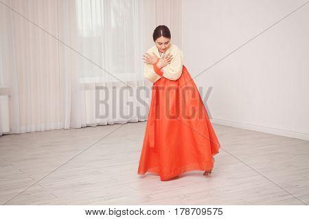 Beautiful young woman in Korean traditional costume dancing at home