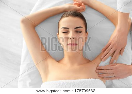 Beautician waxing female armpits in spa center