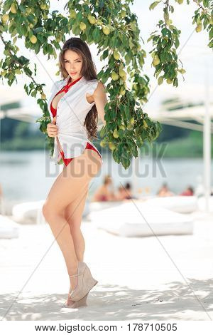 Vacation woman relaxing on beach at pear tree on summer holidays resort. Beautiful happy multiracial Asian Chinese Caucasian young woman in swimsuit standing in full lenght looking at camera.