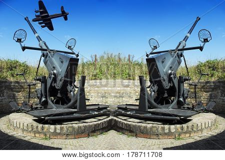 Two old anti-aircraft guns for defense in the background a combat aircraft on the Atlantic Wall