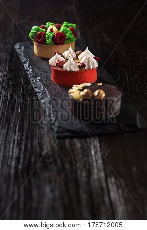 Side view on mini party tartlets with fresh fruit, chocolate, nuts and cream on black slate background. Sweet cakes