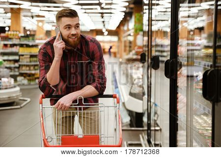 Image of cheerful young man standing in supermarket choosing products while talking by phone. Looking aside.