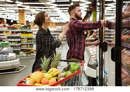 Image of young happy loving couple in supermarket with shopping trolley choosing products. Looking aside.