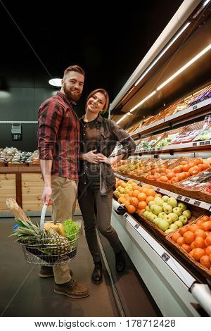 Photo of happy young loving couple standing in supermarket choosing vegetables. Looking at camera.