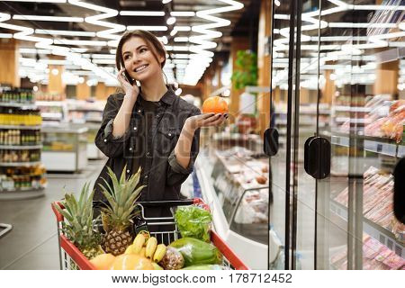 Picture of young cheerful woman in supermarket with shopping trolley choosing products and talking by phone. Looking aside.