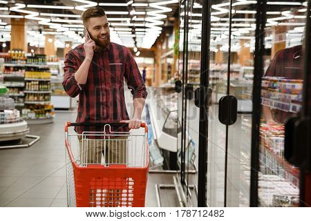 Image of happy young man standing in supermarket choosing products while talking by phone. Looking aside.