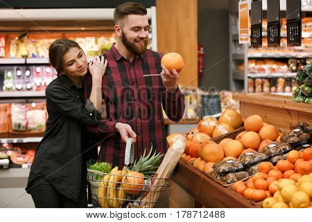 Picture of happy young loving couple standing in supermarket choosing fruits. Looking aside.