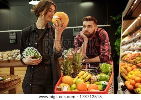 Image of young loving couple in supermarket with shopping trolley choosing fruits. Man looking at woman.
