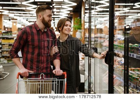 Photo of young happy loving couple standing in supermarket choosing the products. Looking aside.