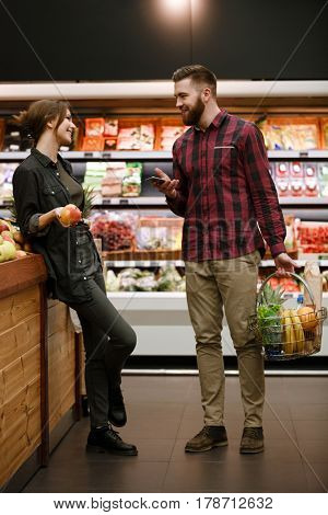 Photo of happy young loving couple standing and talking in supermarket. Looking aside and using phone.