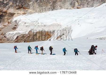 Group of Mountain Climbers walking on snowy Glacier between crevasses and other dangers using climbing and hiking Gear carrying Backpacks