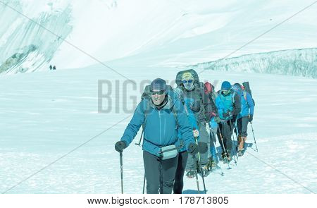 Mature Guide in high altitude Boots and other Gear leading diverse Group of Mountain Climbers on ascent to Himalaya Peak walking on snowy Glacier cool Toned.