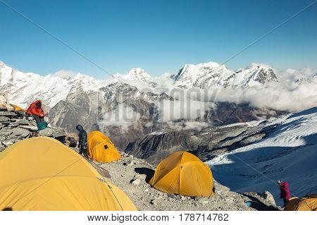 Orange Tents of high Altitude Camp of Mountain Climbers Expedition in Himalaya Nepal in the evening