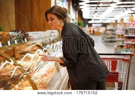 Picture of concentrated young lady standing in supermarket choosing pastries. Looking aside.