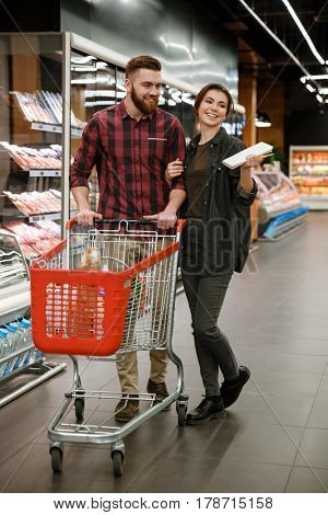 Picture of young happy loving couple standing in supermarket choosing products. Looking aside.