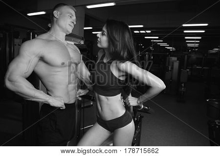 beautiful young sporty sexy couple showing muscle and workout in gym during photoshooting Fitness exercise