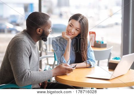 Involved in conversation. Pretty young smiling woman sitting at cafe and intently looking at youthful bearded guy near her.