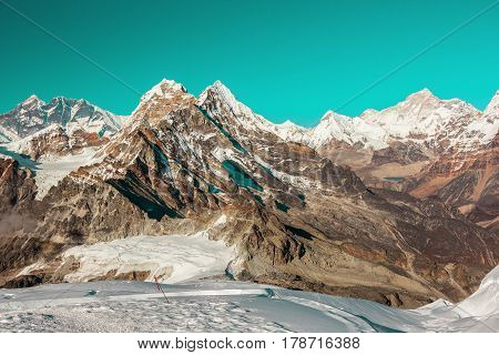 Cosmic coloured View of high Altitude Mountains in Himalaya evening Sunlight unrealistic unusual Sky