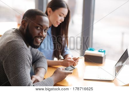 Always in touch. Handsome young man smiling and holing new smartphone while sitting at table near window with his female friend.