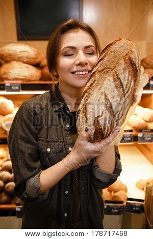 Picture of young smiling woman in supermarket choosing pastries. Eyes closed.