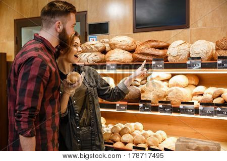 Picture of young happy loving couple in supermarket choosing pastries. Looking aside.
