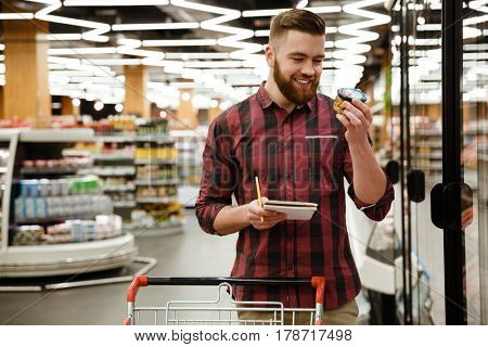 Photo of smiling young man standing in supermarket choosing products while reading notes at notebook. Looking aside.
