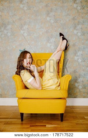 Vertical image of surprised woman in yellow dress which lying on armchair and looking at camera