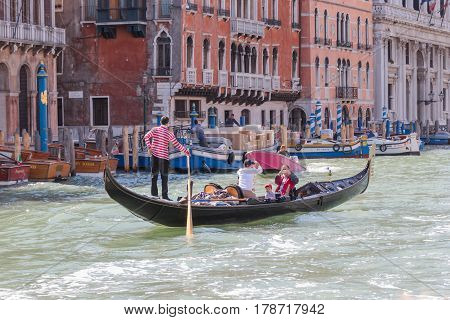 Venice Italy - September 28 2015 : Water channels of Venice city. Gondolier rolls tourists on the gondola on Grand Canal in Venice Italy.