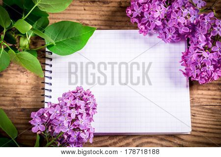 Bunch of lilac with green leaf on brown wood old table with blank notebook, empty space for text