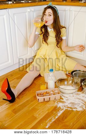Picture of pretty young pin-up woman with red lipstick sitting on floor at kitchen and cooking. Looking at camera while drinking juice.