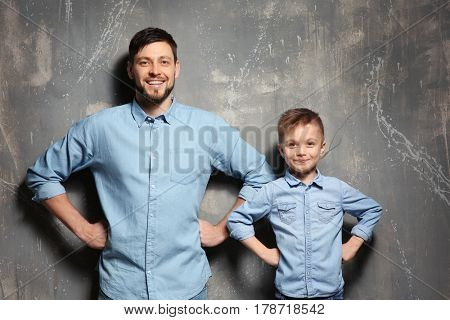 Handsome man with his son near grunge wall