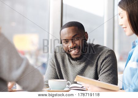 Friendly smile. Young handsome bearded man smiling and looking at his female friend holding book at cafeteria.