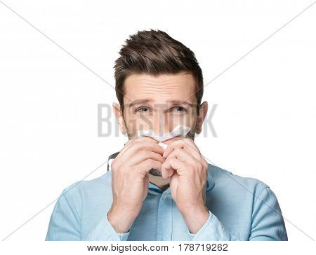 Young man using tissue to blow his nose on light background