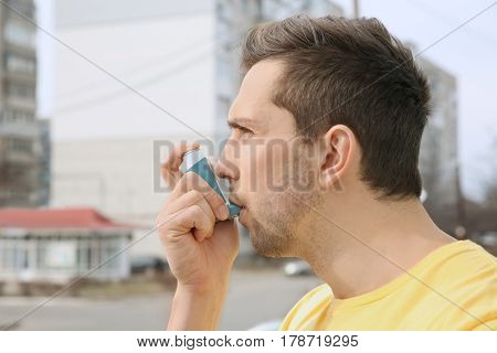 Young man using inhaler during asthmatic attack outdoors