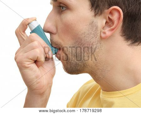 Young man using inhaler during asthmatic attack on white background, closeup