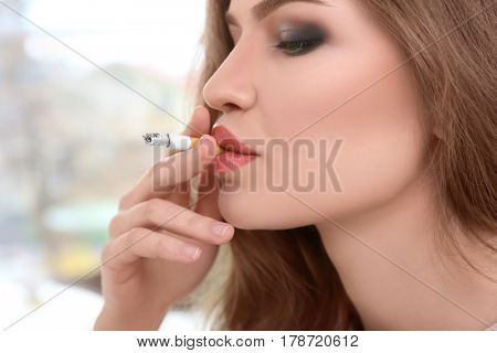 Young smoking woman's portrait in profile, closeup