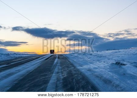 A lonely trucker driving in the blizzard at the dusk in blue tones