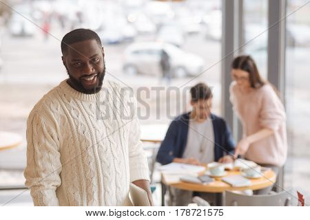 Satisfied with life. Happy nice mulatto man standing at cafeteria on background of his working fellow students.