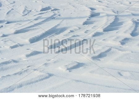 Curvy car tracks in the snow at daytime background