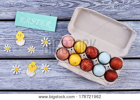 Easter eggs and decorations. Egg tray and wooden background. Easter festive greetings.