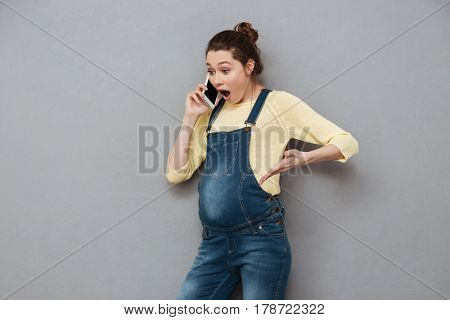Portrait of a surprised shocked pregnant woman standing and talking on mobile phone isolated on a gray background