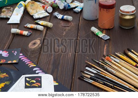 Art brushes and oil paints and sketches are laid out on a dark wooden surface