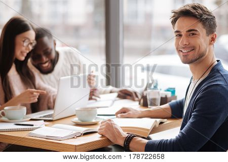 Studying together. Young handsome guy smiling while sitting at cafe on background of his studying fellow students.