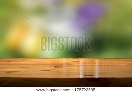 blurred springbackground with wooden desk in the foreground