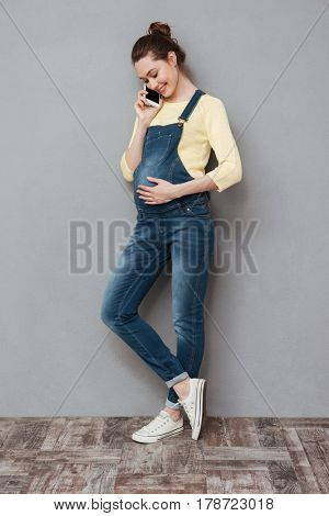 Full length portrait of a cute young pregnant woman standing and talking on mobile phone isolated on a gray background